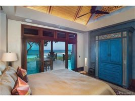 The home has two direct oceanfront Master Bedroom suites. This Master Bedroom features the same handcrafted Teak and Merbau hardwood finishes found throughout the home with direct access onto the covered lanai.